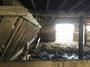 The inside of the barn with extra hay to feed to the cattle.